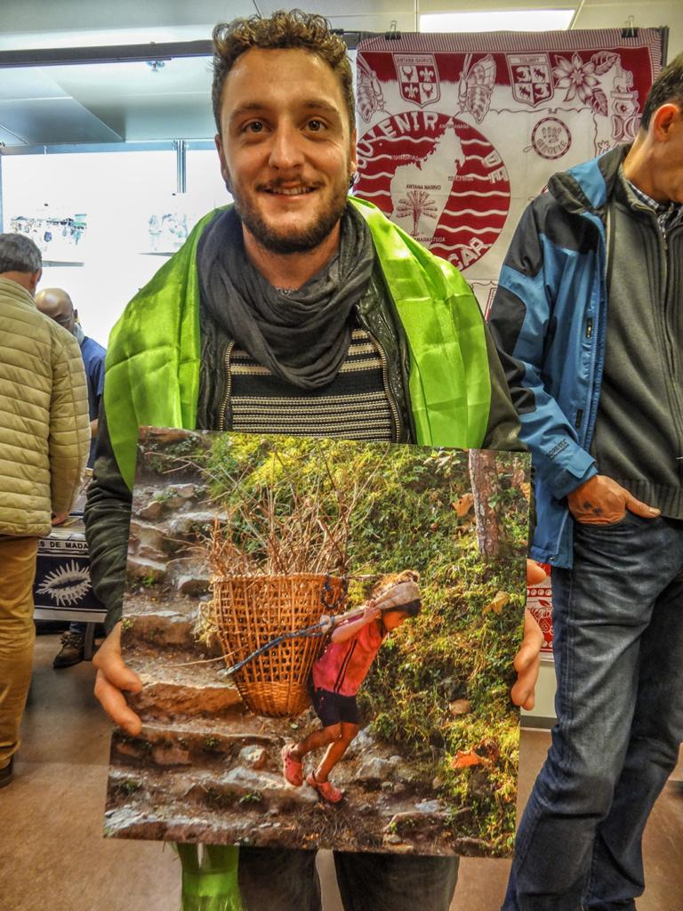 Vincent présente une des photos à vendre, prise au village de Basa Rapcha